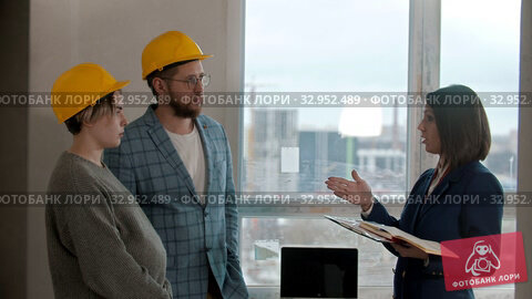 A pregnant woman with her husband looking out in new apartment - a man talking to a real estate agent. Стоковое видео, видеограф Константин Шишкин / Фотобанк Лори