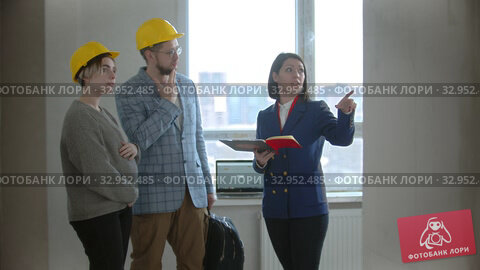 A pregnant woman with her husband with a real estate agent in apartment in a new building - man asking questions to a woman agent. Стоковое видео, видеограф Константин Шишкин / Фотобанк Лори