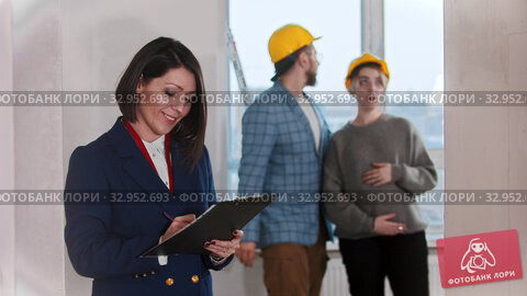 A real estate agent confident woman signing papers and smiling in draft apartment - young married couple looking around on the background. Стоковое видео, видеограф Константин Шишкин / Фотобанк Лори