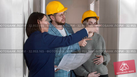 A real estate agent showing a new draft apartment to a young successful married couple holding a layout on the paper. Стоковое видео, видеограф Константин Шишкин / Фотобанк Лори