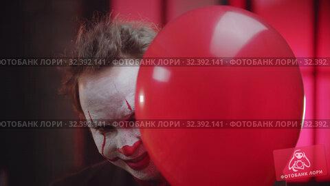 Купить «A scary clown with cracked paint on the face peeking out from the red balloon and creepy smiling», видеоролик № 32392141, снято 19 ноября 2019 г. (c) Константин Шишкин / Фотобанк Лори