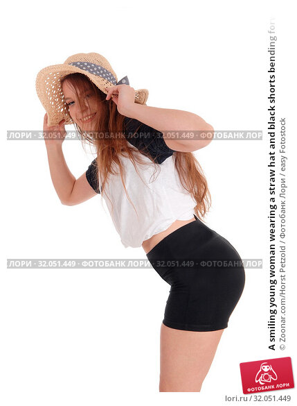 A smiling young woman wearing a straw hat and black shorts bending forwards and smiling, isolated for white background. Стоковое фото, фотограф Zoonar.com/Horst Petzold / easy Fotostock / Фотобанк Лори