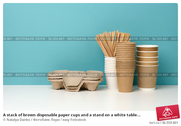 A stack of brown disposable paper cups and a stand on a white table... Стоковое фото, фотограф Natalya Danko / easy Fotostock / Фотобанк Лори