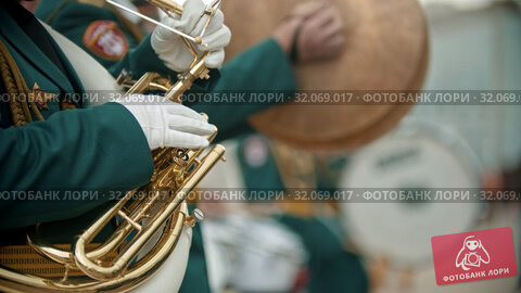 A wind instrument military parade - a man in green costume playing french horn outdoors. Стоковое видео, видеограф Константин Шишкин / Фотобанк Лори