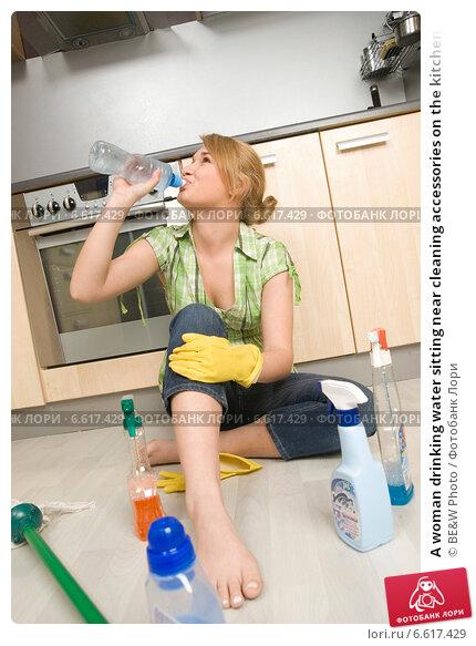 Купить «A woman drinking water sitting near cleaning accessories on the kitchen floor.», фото № 6617429, снято 19 марта 2019 г. (c) BE&W Photo / Фотобанк Лори
