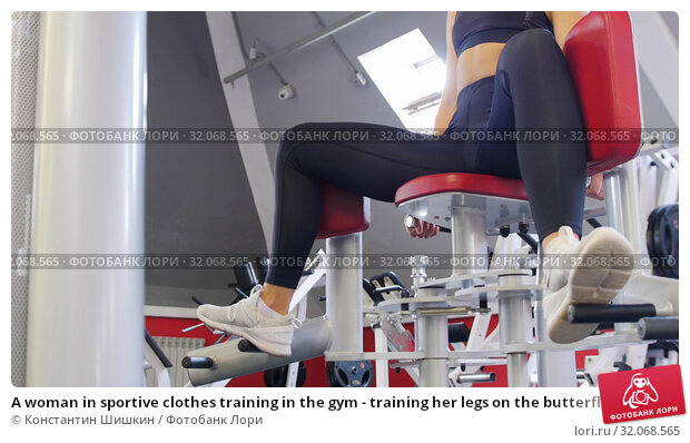 A woman in sportive clothes training in the gym - training her legs on the butterfly training apparatus. Стоковое фото, фотограф Константин Шишкин / Фотобанк Лори