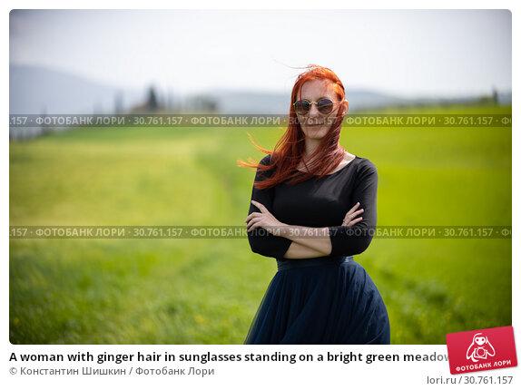 Купить «A woman with ginger hair in sunglasses standing on a bright green meadow», фото № 30761157, снято 24 апреля 2019 г. (c) Константин Шишкин / Фотобанк Лори
