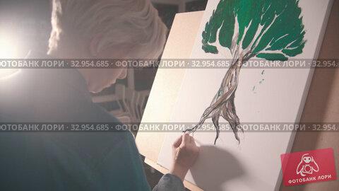 A young blonde woman artist painting a tree root in darker color. Стоковое видео, видеограф Константин Шишкин / Фотобанк Лори