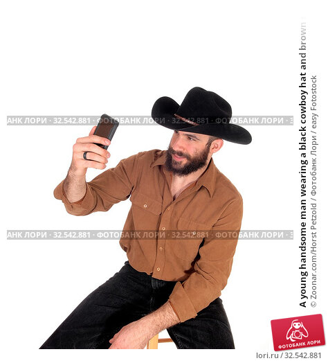 Купить «A young handsome man wearing a black cowboy hat and brown shirt taking a selfie with his cell phone, isolated for white background», фото № 32542881, снято 9 декабря 2019 г. (c) easy Fotostock / Фотобанк Лори