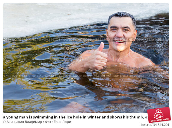 a young man is swimming in the ice hole in winter and shows his thumb, excellent. Редакционное фото, фотограф Акиньшин Владимир / Фотобанк Лори