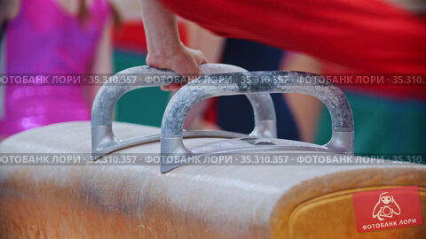 A young person exercising on the gymnastic horse with handles on the tournament -swings with the feet. Стоковое видео, видеограф Константин Шишкин / Фотобанк Лори
