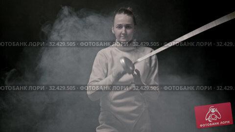 Купить «A young smiling woman fencer throwing up her sword in the air and catching it», видеоролик № 32429505, снято 3 апреля 2020 г. (c) Константин Шишкин / Фотобанк Лори