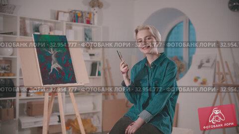 A young woman artist sits on the chair on the art studio holding brushes. Стоковое видео, видеограф Константин Шишкин / Фотобанк Лори
