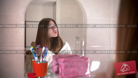 A young woman brushes her thick hair looking in the mirror. Стоковое видео, видеограф Константин Шишкин / Фотобанк Лори
