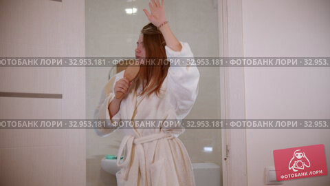 A young woman dancing and singing with a hair brush in her hand wearing a bathrobe - walking in the bathroom. Стоковое видео, видеограф Константин Шишкин / Фотобанк Лори