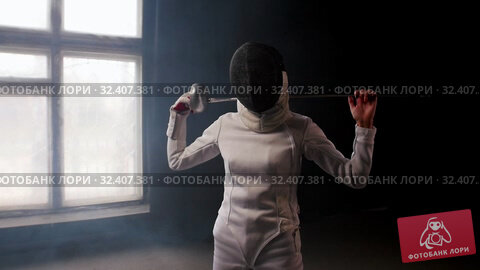 Купить «A young woman fencer putting the sword behind her shoulders», видеоролик № 32407381, снято 31 марта 2020 г. (c) Константин Шишкин / Фотобанк Лори