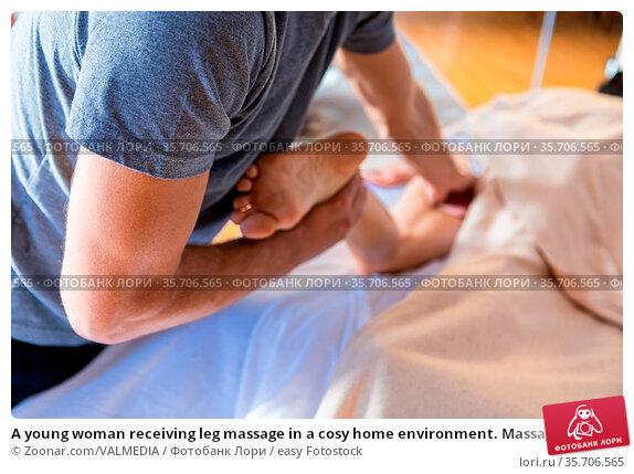 A young woman receiving leg massage in a cosy home environment. Massage... Стоковое фото, фотограф Zoonar.com/VALMEDIA / easy Fotostock / Фотобанк Лори