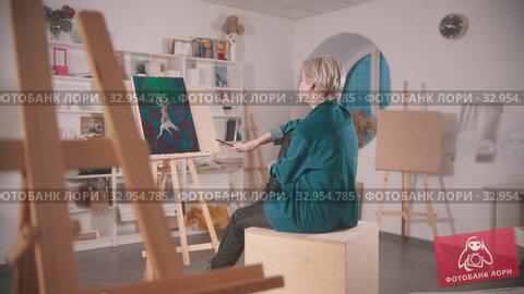 Купить «A young woman with short blonde hair sitting in the art studio - looking at her painting from the distance holding brushes», видеоролик № 32954785, снято 30 мая 2020 г. (c) Константин Шишкин / Фотобанк Лори