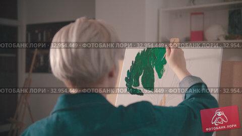 Купить «A young woman with short hair painting upper branches of tree in green color in the art studio», видеоролик № 32954449, снято 31 мая 2020 г. (c) Константин Шишкин / Фотобанк Лори