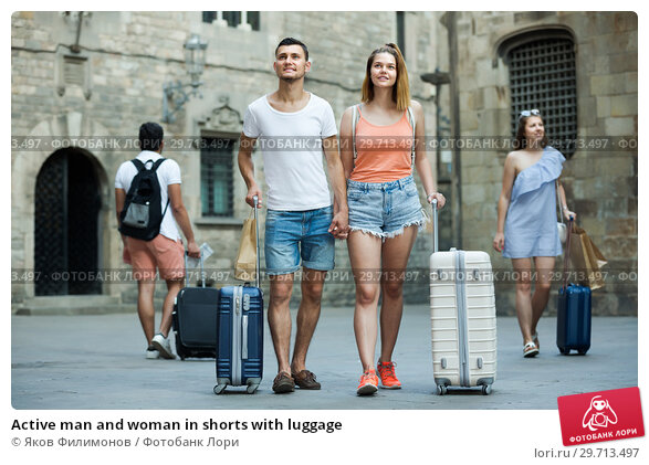 Купить «Active man and woman in shorts with luggage», фото № 29713497, снято 22 июня 2017 г. (c) Яков Филимонов / Фотобанк Лори