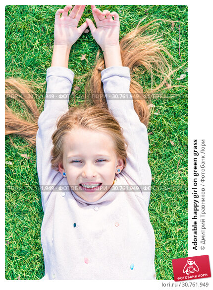 Купить «Adorable happy girl on green grass», фото № 30761949, снято 29 апреля 2017 г. (c) Дмитрий Травников / Фотобанк Лори