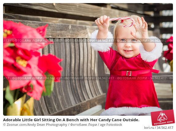 Adorable Little Girl Sitting On A Bench with Her Candy Cane Outside. Стоковое фото, фотограф Zoonar.com/Andy Dean Photography / age Fotostock / Фотобанк Лори