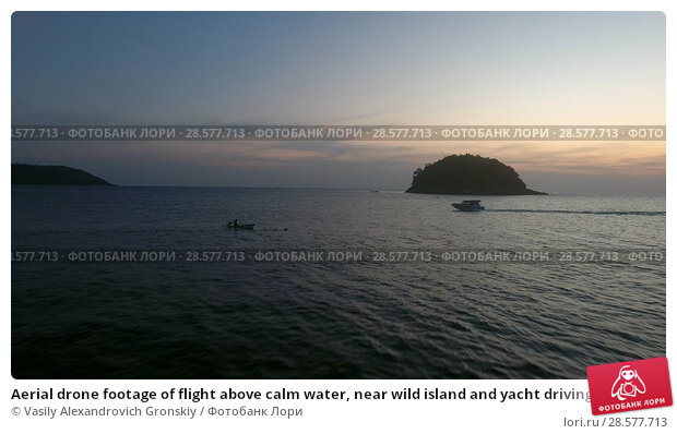 Купить «Aerial drone footage of flight above calm water, near wild island and yacht driving in sunset soft ligh», фото № 28577713, снято 16 января 2019 г. (c) Vasily Alexandrovich Gronskiy / Фотобанк Лори