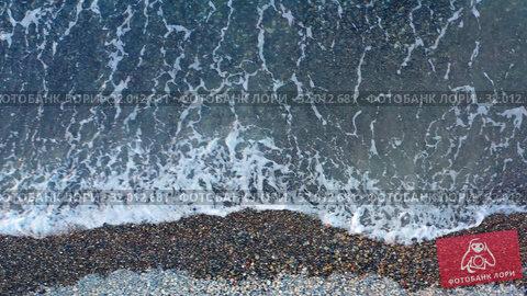 Купить «Aerial video of pebble beach natural background. Camera looks down with movement along surf line.», видеоролик № 32012681, снято 14 июля 2019 г. (c) Serg Zastavkin / Фотобанк Лори