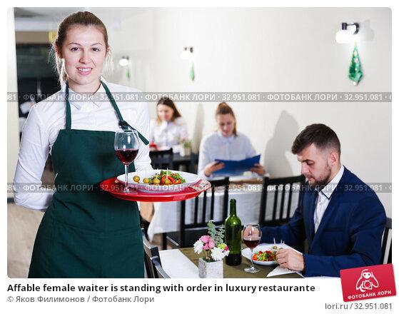 Affable female waiter is standing with order in luxury restaurante. Стоковое фото, фотограф Яков Филимонов / Фотобанк Лори