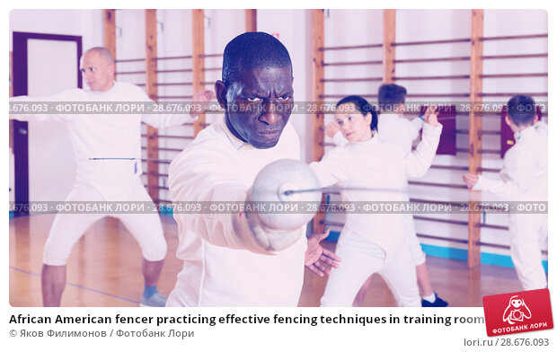 Купить «African American fencer practicing effective fencing techniques in training room», фото № 28676093, снято 30 мая 2018 г. (c) Яков Филимонов / Фотобанк Лори
