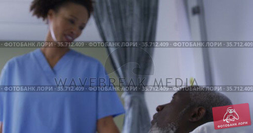 African american male patient in hospital bed talking with mixed race female doctor. Стоковое видео, агентство Wavebreak Media / Фотобанк Лори