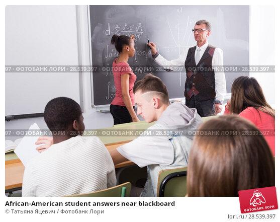 Купить «African-American student answers near blackboard», фото № 28539397, снято 18 июня 2018 г. (c) Татьяна Яцевич / Фотобанк Лори