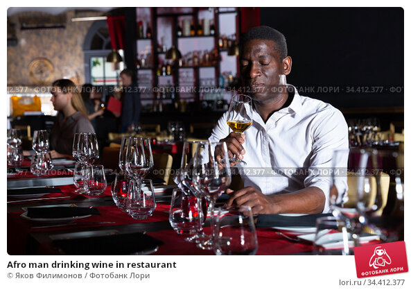 Afro man drinking wine in restaurant. Стоковое фото, фотограф Яков Филимонов / Фотобанк Лори
