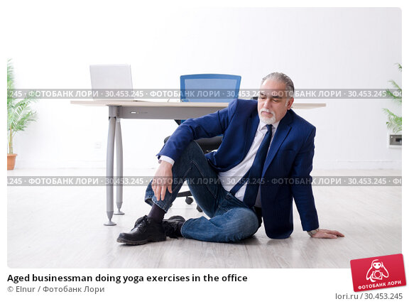 Aged businessman doing yoga exercises in the office. Стоковое фото, фотограф Elnur / Фотобанк Лори