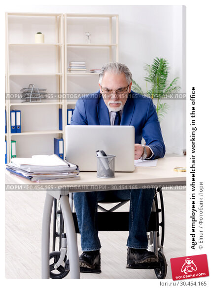 Aged employee in wheelchair working in the office. Стоковое фото, фотограф Elnur / Фотобанк Лори