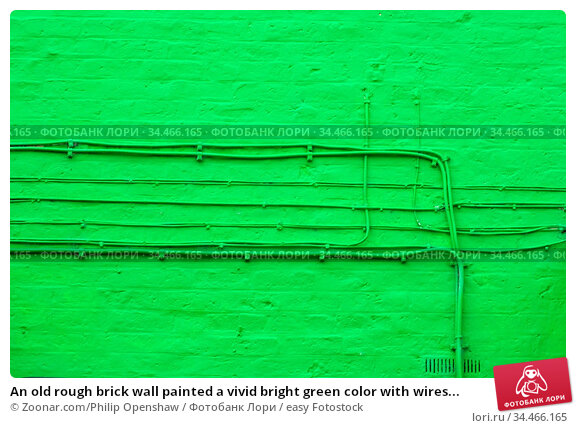 An old rough brick wall painted a vivid bright green color with wires... Стоковое фото, фотограф Zoonar.com/Philip Openshaw / easy Fotostock / Фотобанк Лори