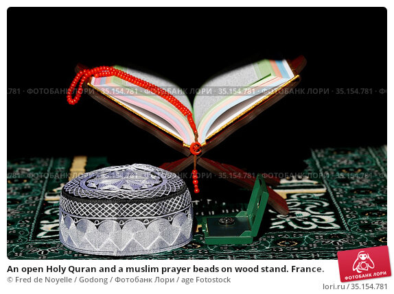 An open Holy Quran and a muslim prayer beads on wood stand. France. Стоковое фото, фотограф Fred de Noyelle / Godong / age Fotostock / Фотобанк Лори
