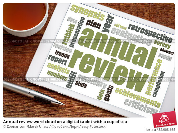 Annual review word cloud on a digital tablet with a cup of tea. Стоковое фото, фотограф Zoonar.com/Marek Uliasz / easy Fotostock / Фотобанк Лори