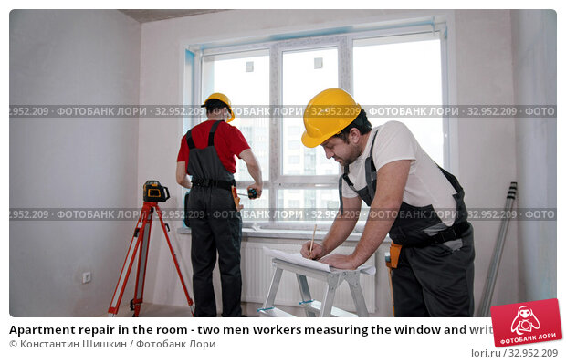 Apartment repair in the room - two men workers measuring the window and writing notes about it. Стоковое фото, фотограф Константин Шишкин / Фотобанк Лори