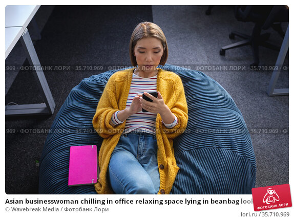 Asian businesswoman chilling in office relaxing space lying in beanbag looking at smartphone. Стоковое фото, агентство Wavebreak Media / Фотобанк Лори