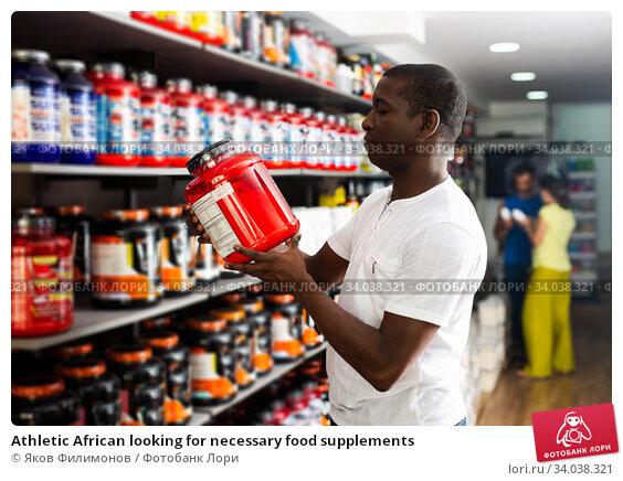 Athletic African looking for necessary food supplements. Стоковое фото, фотограф Яков Филимонов / Фотобанк Лори