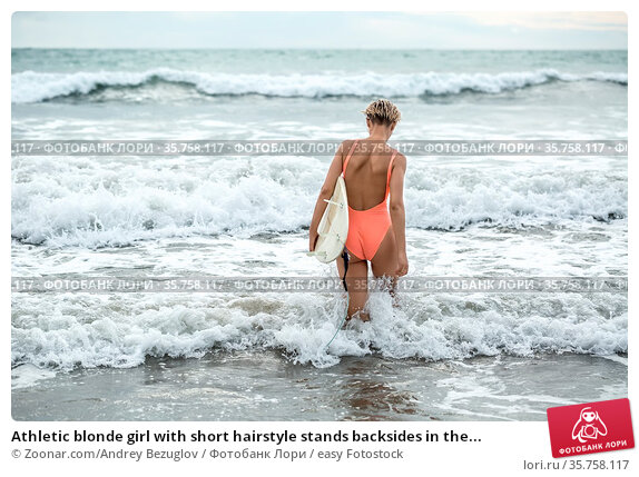 Athletic blonde girl with short hairstyle stands backsides in the... Стоковое фото, фотограф Zoonar.com/Andrey Bezuglov / easy Fotostock / Фотобанк Лори