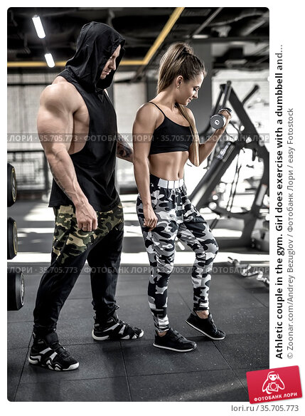 Athletic couple in the gym. Girl does exercise with a dumbbell and... Стоковое фото, фотограф Zoonar.com/Andrey Bezuglov / easy Fotostock / Фотобанк Лори