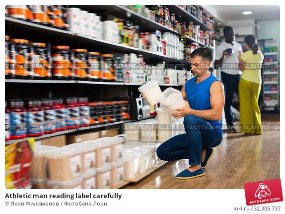 Купить «Athletic man reading label carefully», фото № 32305737, снято 18 января 2020 г. (c) Яков Филимонов / Фотобанк Лори