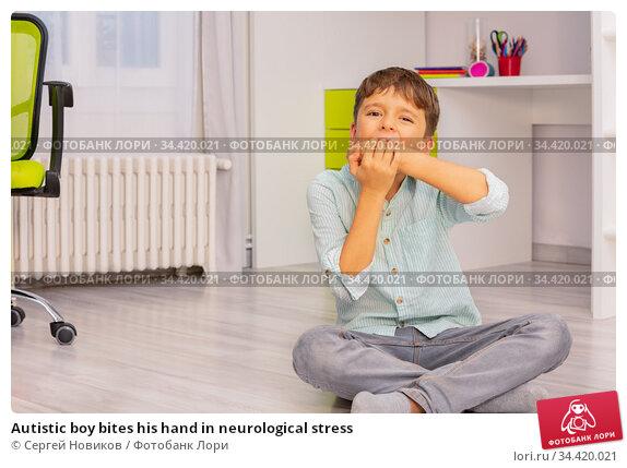 Autistic boy bites his hand in neurological stress. Стоковое фото, фотограф Сергей Новиков / Фотобанк Лори