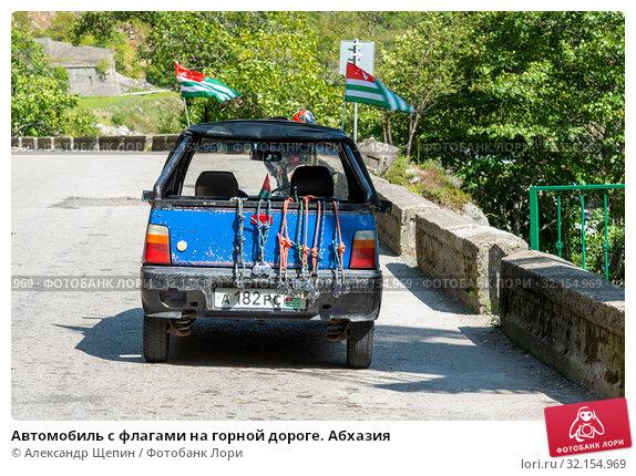 Купить «Автомобиль с флагами на горной дороге. Абхазия», эксклюзивное фото № 32154969, снято 11 сентября 2017 г. (c) Александр Щепин / Фотобанк Лори