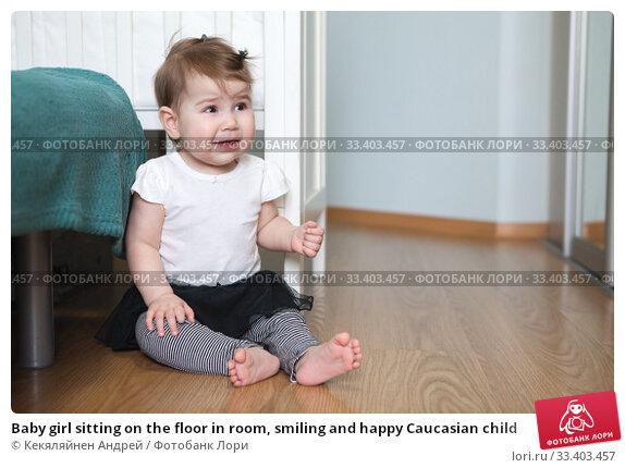 Купить «Baby girl sitting on the floor in room, smiling and happy Caucasian child», фото № 33403457, снято 8 марта 2020 г. (c) Кекяляйнен Андрей / Фотобанк Лори