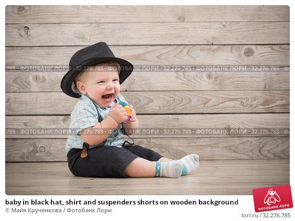 Купить «baby in black hat, shirt and suspenders shorts on wooden background», фото № 32276785, снято 7 октября 2019 г. (c) Майя Крученкова / Фотобанк Лори