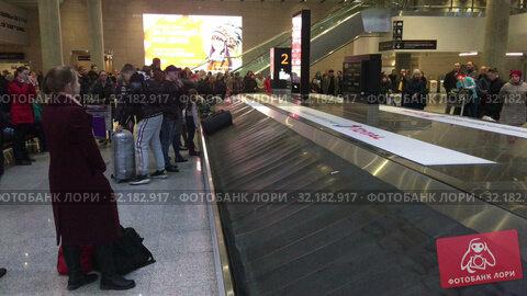 Купить «Bags and suits come on baggage conveyor belt in baggage delivery area. Arrival lounge of the Pulkovo International airport. Passengers find their things», видеоролик № 32182917, снято 2 апреля 2019 г. (c) Кекяляйнен Андрей / Фотобанк Лори