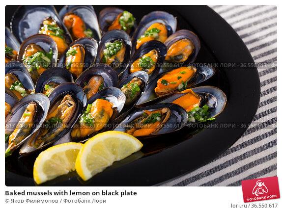 Baked mussels with lemon on black plate. Стоковое фото, фотограф Яков Филимонов / Фотобанк Лори